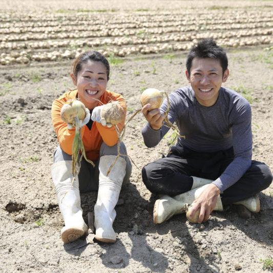 畑で座る農家の若い夫婦